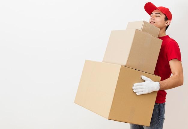 Copia espacio entrega macho llevando pila de paquetes
