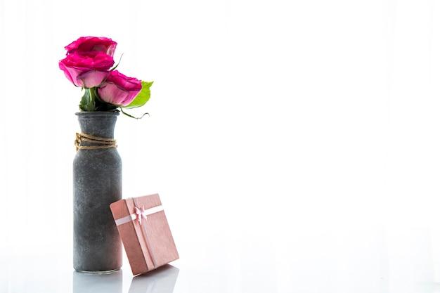 Copia espacio jarrón de rosas con regalo.