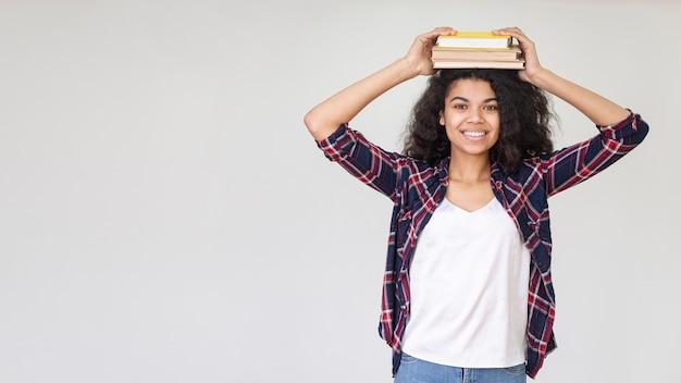 Copia-espacio juguetón adolescente con libro en la cabeza.