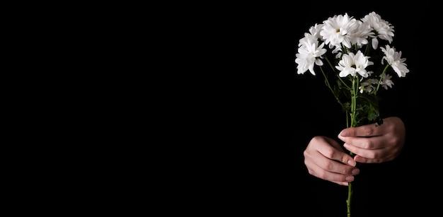 Copia espacio mano con ramo de flores