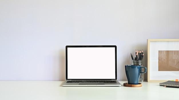 Copia espacio maqueta portátil, taza de café, lápiz con marco de fotos en el escritorio del espacio de trabajo.
