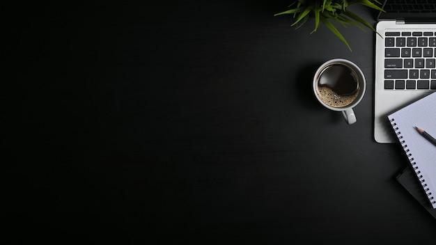 Copia espacio mesa de oficina negro con laptop, cuaderno, lápiz y taza de café con plat.