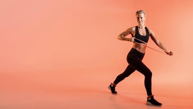 Copia espacio mujer entrenando con banda elástica