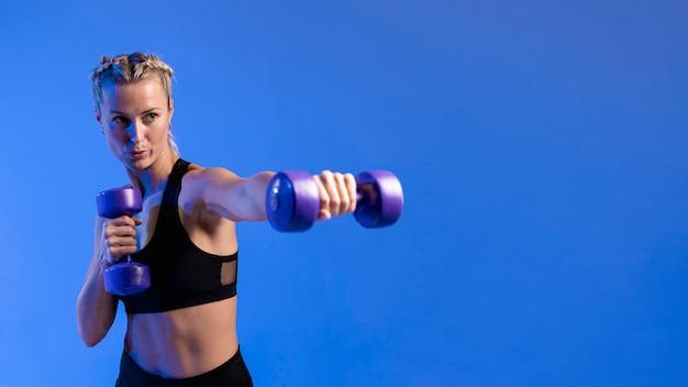 Copia espacio mujer entrenando con pesas
