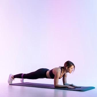 Copia-espacio mujer haciendo ejercicio en mat
