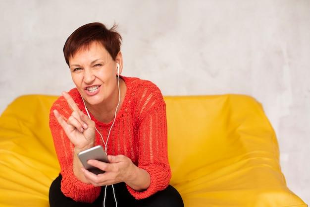 Copia espacio mujer en sofá muestra signo de rock