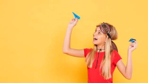 Copia-espacio niña jugando con avión de papel
