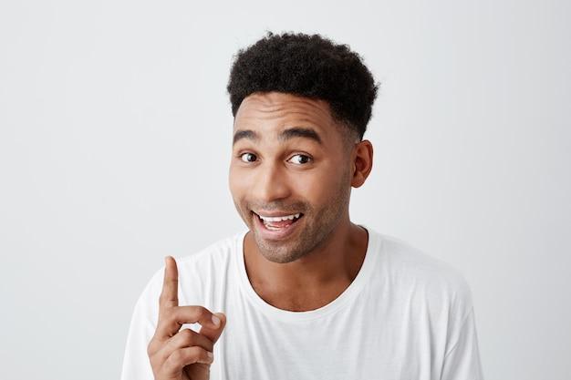 Copia espacio retrato de joven atractivo hombre alegre de piel negra con peinado afro en camiseta casual sonriendo con dientes, apuntando al revés con el dedo, mirando a la cámara con expresión feliz