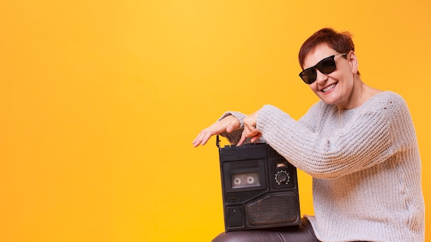 Copia espacio senior femenino sosteniendo cassette