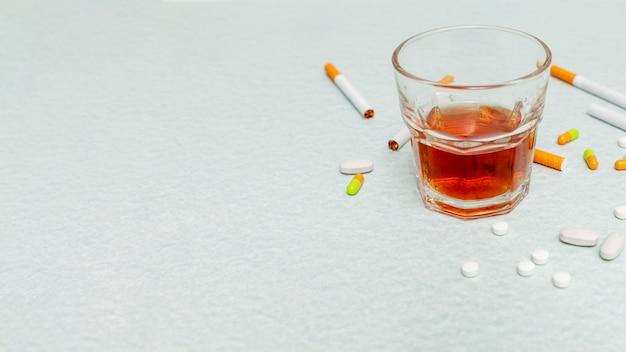 Copia espacio de vidrio con alcohol y cigarrillos.