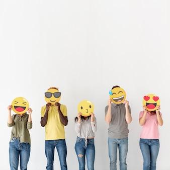 Copiar espacio jóvenes cubriendo cabezas con emoji
