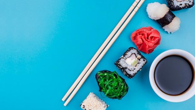Copiar rollos de sushi alineados con salsa de soja