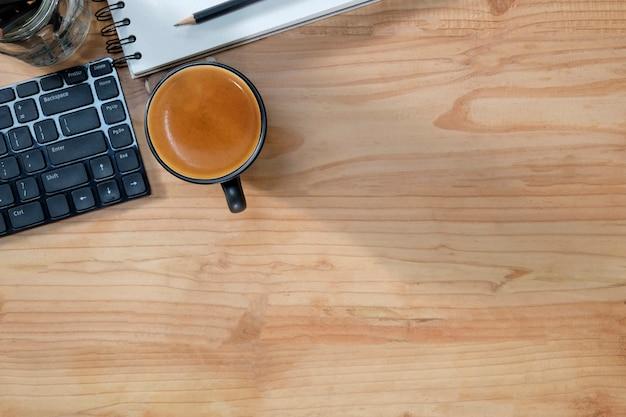 Copie el café del escritorio de oficina del espacio, la libreta, el lápiz y el teclado de ordenador en la tabla de madera.