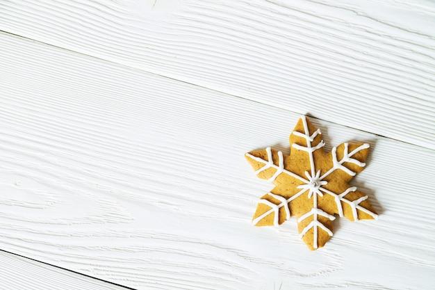 Copie el espacio con la galleta de jengibre de navidad en forma de copo de nieve sobre fondo blanco de madera. vista superior.