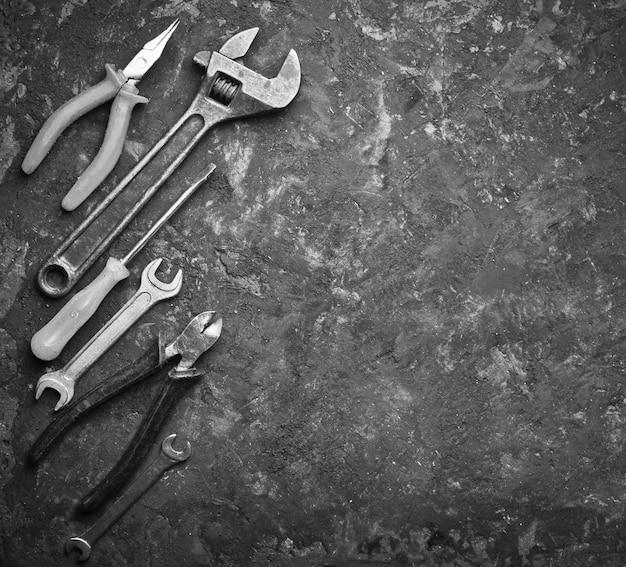 Copie el espacio de las herramientas de trabajo sobre una superficie de hormigón negro. pinzas, llaves, alicates, destornillador. vista superior.