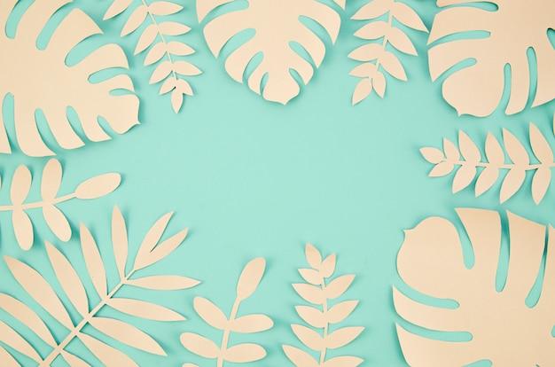 Copie el espacio y las hojas tropicales en papel cortado