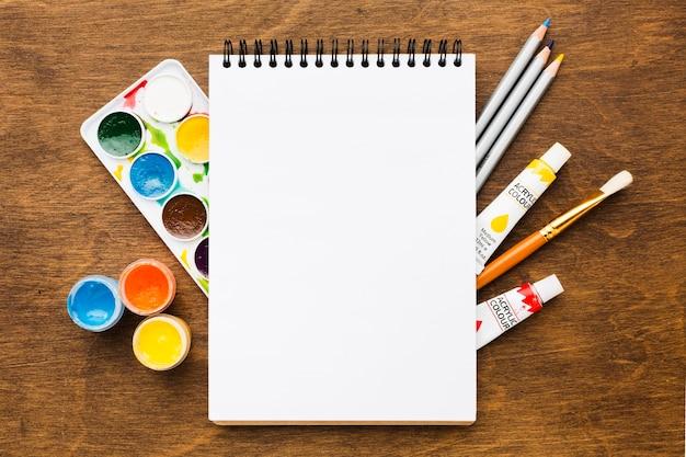 Copie el espacio libreta encima de las herramientas de pintura