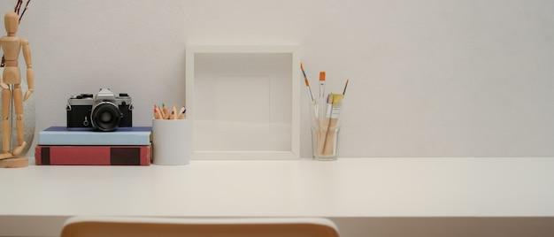 Copie el espacio en la mesa de estudio con marco simulado, herramientas de pintura, cámara, libros en el escritorio blanco