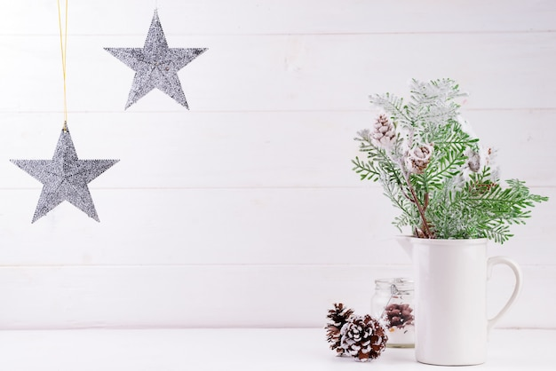 Copie el espacio con ramas de pino en florero, estrellas en madera blanca
