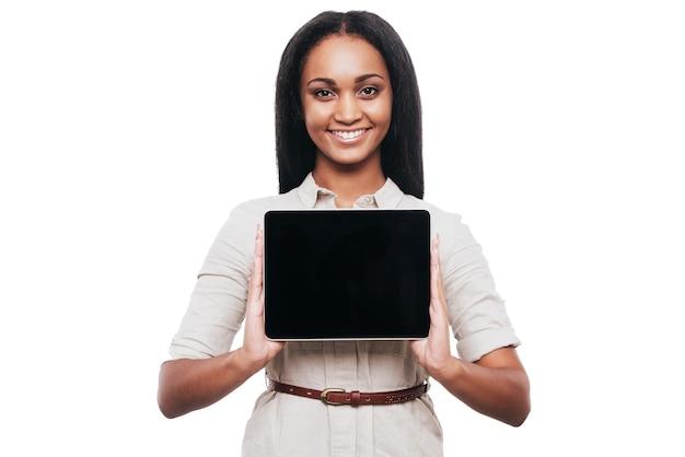 Copie el espacio en su pestaña. confianza joven africana mostrando su tableta digital y sonriendo mientras está de pie contra el fondo blanco.