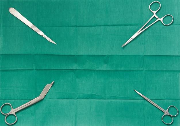 Copie el espacio de texto con la cuchilla de cirugía, tijeras, agarre de calambre, baum en marco lateral en el fondo vestido verde