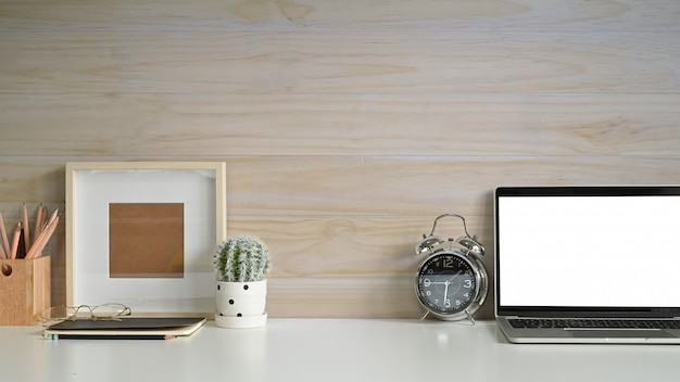 Copie el espacio de trabajo portátil maqueta portátil, marco de fotos, reloj despertador y cactus en el escritorio con pared de madera.