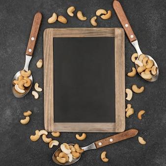 Copie el marco del espacio y cucharas llenas de anacardos