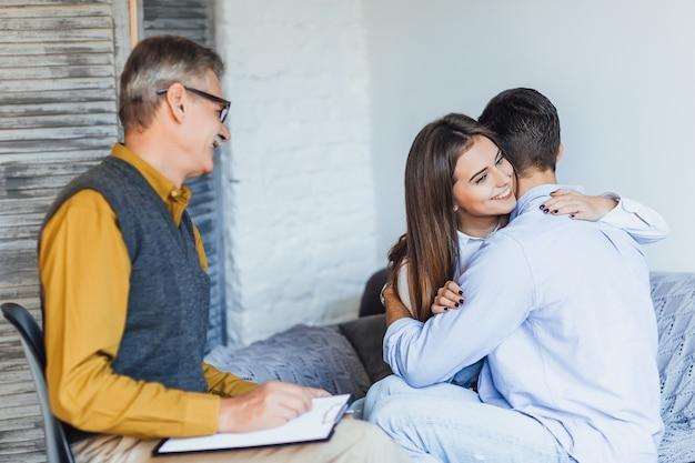 Cople casado feliz en la oficina del psicólogo con emociones sinceras