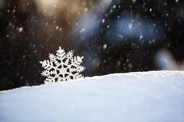 Copo de nieve en la nieve. vacaciones de invierno y fondo de navidad.