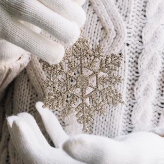 Copo de nieve de plata en las manos