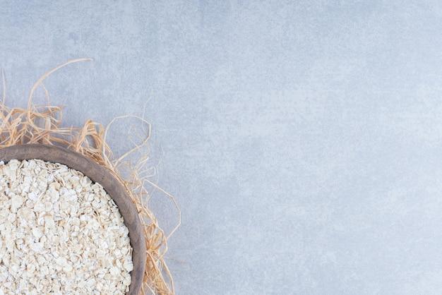 Copos de avena apilados en un pequeño cuenco de madera encima de un montón de paja sobre fondo de mármol.