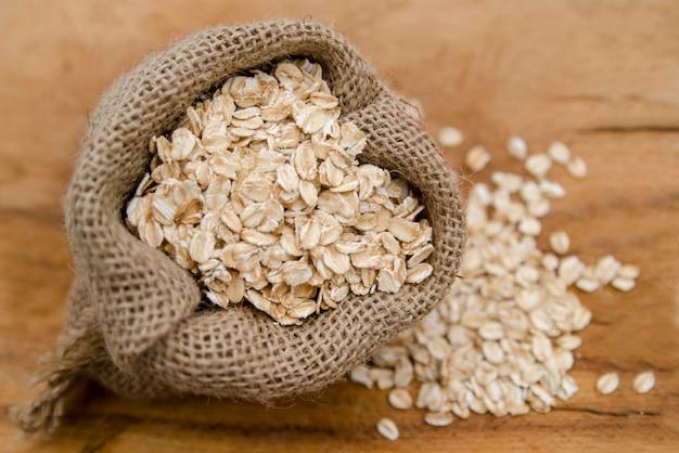 Copos de avena en bolsa de tela de cerca. cereal saludable para el desayuno
