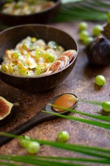 Copos de avena con coco, bayas de grosella, salsa de caramelo e higo