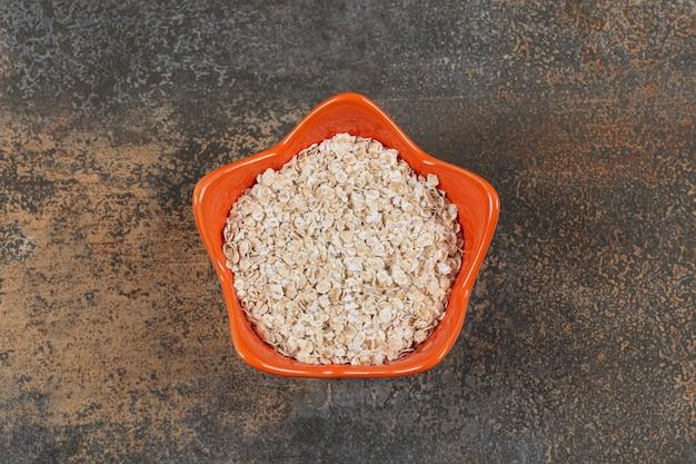 Copos de avena deliciosos en tazón de fuente naranja.