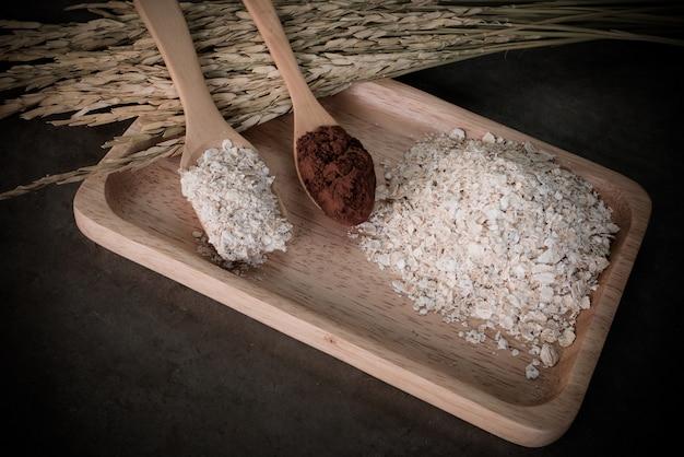 Los copos de avena que se mezclan con el polvo de coco en el escritorio, se preparan para la salud.