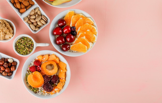 Copos de avena en tazones con frutas, nueces, mantequilla de maní