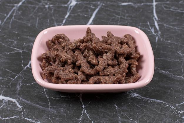 Copos de cereales de chocolate en un tazón de color rosa.