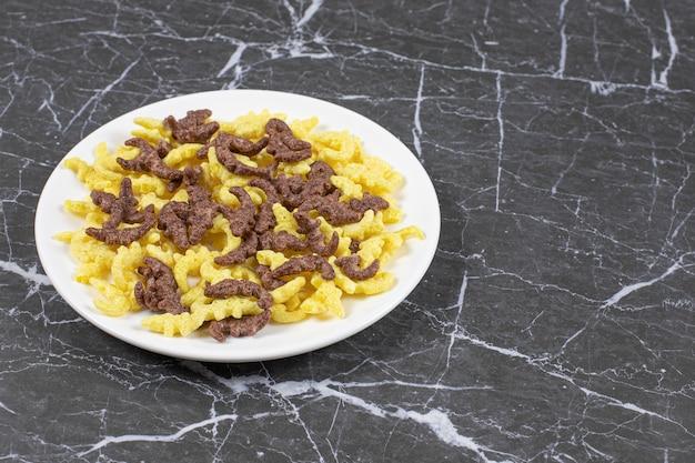 Copos de cereales esparcidos en un plato blanco.