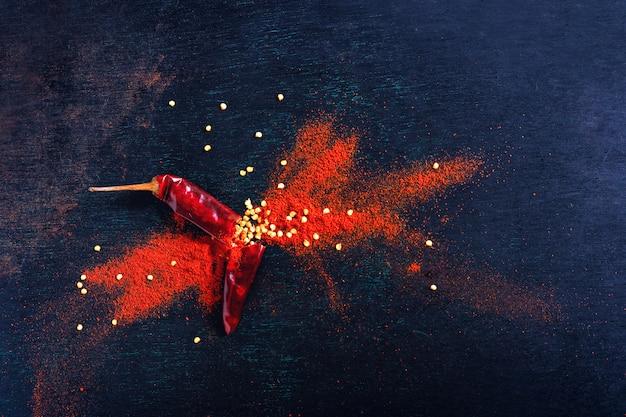 Copos de chile rojo y polvo de chile estalló sobre fondo negro