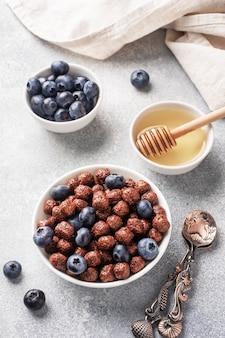 Copos de chocolate hechos de cereales naturales con arándanos frescos, miel y leche