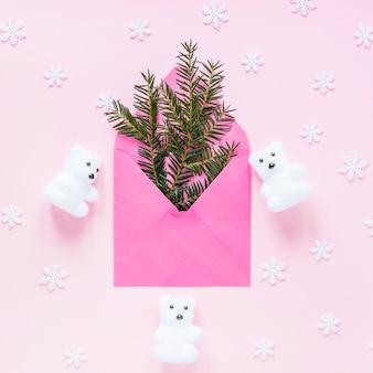 Copos de nieve y osos alrededor de sobre con ramas de coníferas
