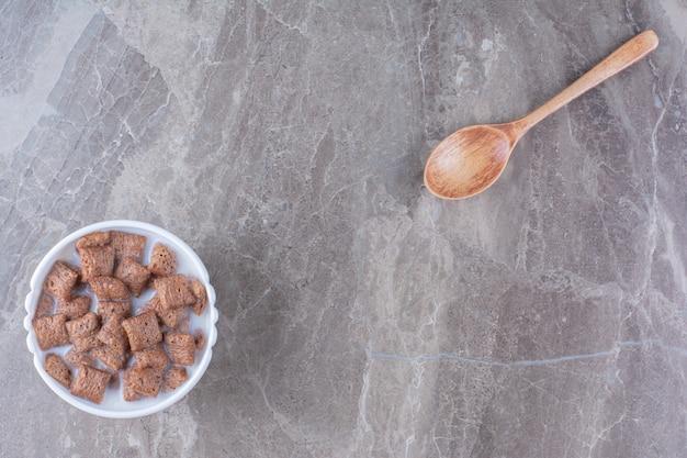 Copos de maíz de almohadillas de chocolate en un tazón blanco con una cuchara de madera.