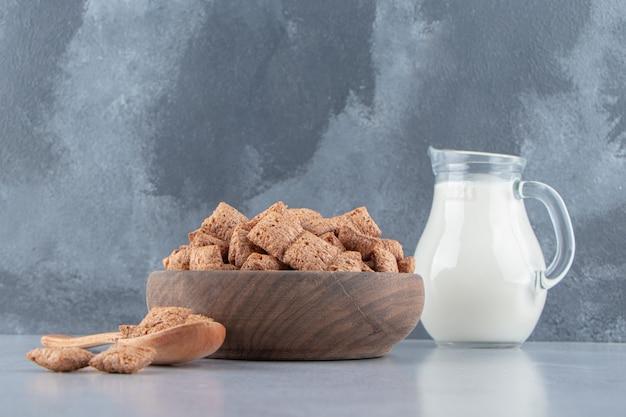 Copos de maíz de almohadillas de chocolate en un tazón de madera con una botella de leche. foto de alta calidad