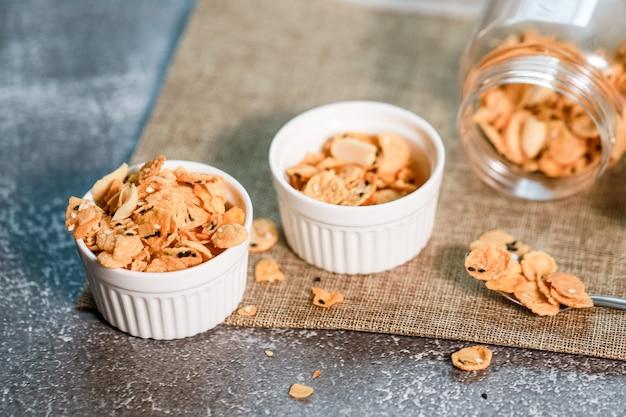 Los copos de maíz y los granos en el tazón blanco son un buen desayuno en lácteos para un buen sabor fresco y saludable en todos los días.