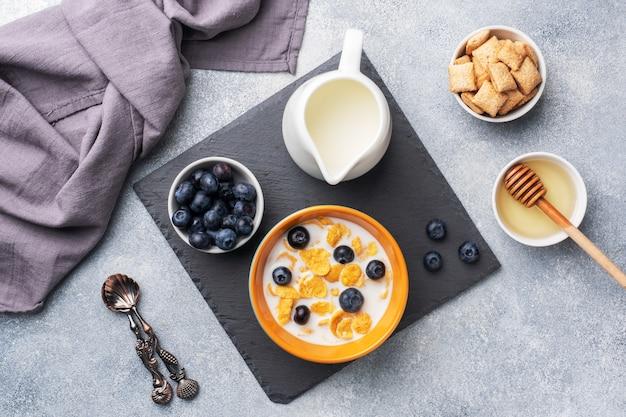 Copos de maíz hechos de cereales naturales con arándanos frescos, miel y leche