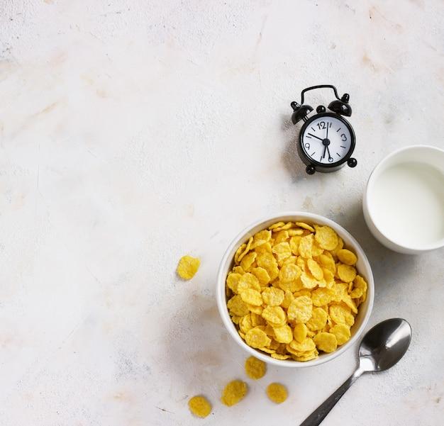 Copos de maíz, leche, despertador sobre un fondo claro