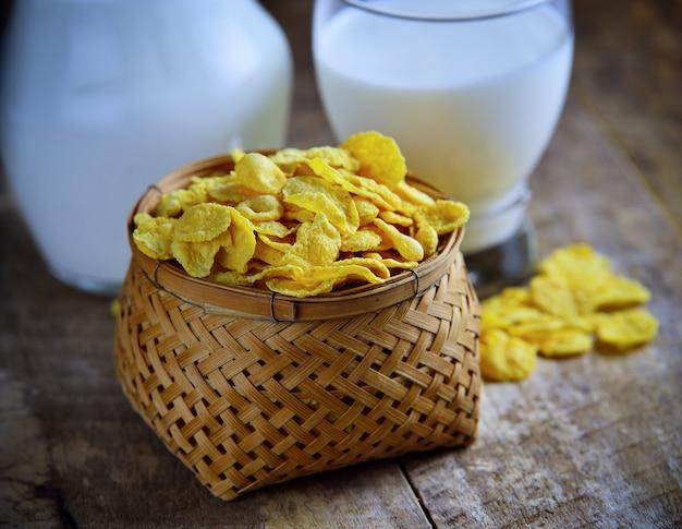 Copos de maíz y leche en la mesa de madera