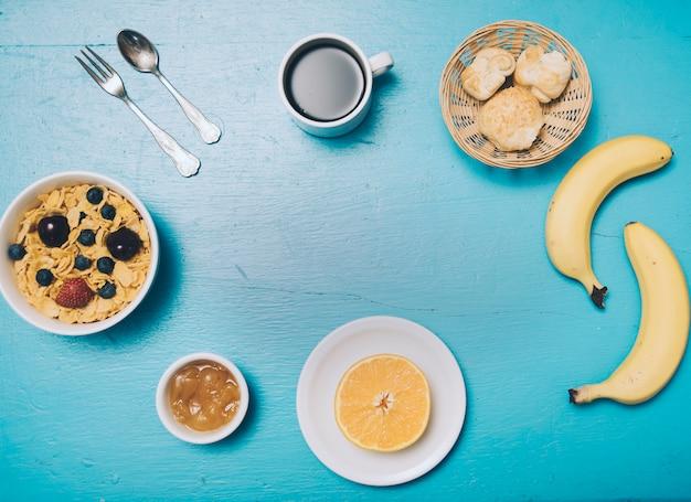 Copos de maíz; mermelada; naranja a la mitad; un pan; café; plátano en el fondo de madera azul