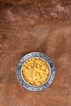 Copos de maíz en una placa en un fondo marrón.