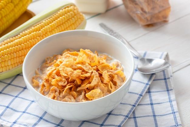 Copos de maíz en un tazón con leche y cereales en un paquete de plástico